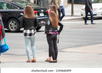 Montreal, Quebec/Canada- 05/18/2016: Attractive young women wait to cross a street in Montreal.