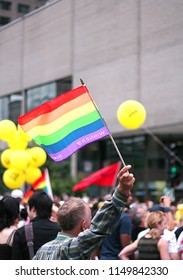 Montreal, Quebec/Canada - August 15, 2010:   Man waves Gay Pride colored flag at the pride parade in the downtown core