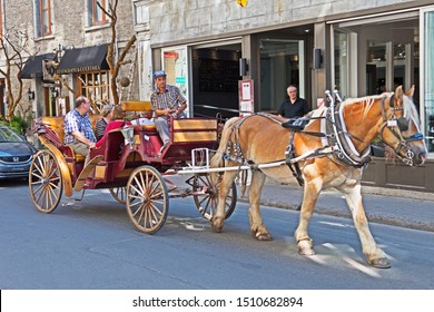 Montreal, Quebec/Canada - September 21 2019: a horse and carriage makes it's way along a street in the old town of Montreal.