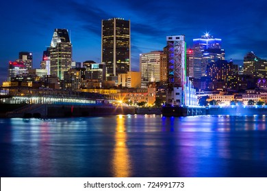 Montreal, September 20, 2017. Spectacular Montreal skyline view seen at dusk with city lights reflecting onto the Ste Lawrence river.