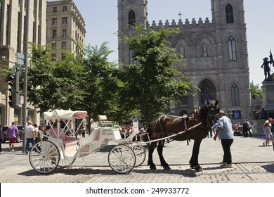 MONTREAL/CANADA - JULY 11, 2014: Horse-drawn carriage on Place d'Armes in front of Notre-Dame Basilica in Montreal.