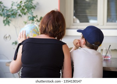 Montreuil-sur-Mer, Hauts-de-France/France-July 14 2018: Mother and son — a mother and son regard the spinning globe they have just bought at a French brocante as they sit in the shade of a restaurant