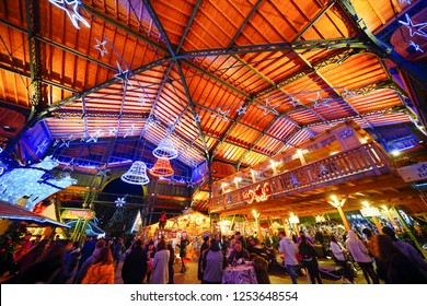 Montreux, Switzerland. 7th December 2018. People are walking through the Montreux Christmas market at night against the backdrop of vibrant illuminated buildings