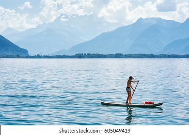 Montreux, Switzerland - August 27, 2016: Girl standing on standup paddle surfing on Geneva Lake in Montreux, Vaud canton, Switzerland