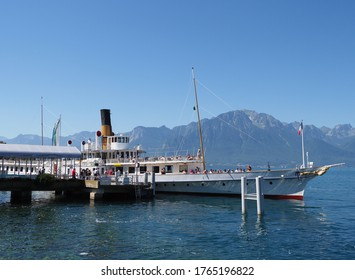 MONTREUX, SWITZERLAND on JULY 2017: Paddle-wheel steam boat moored ready to cruise at promenade on Geneva Lake in european city in canton Vaud, clear blue sky in warm sunny summer day.