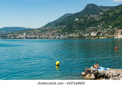 Montreux, VD / Switzerland - 31 May 2019: view of the idyllic lakeshore of Lake Geneva and the Montreux Riviera with people subathing on a beautiful summer day