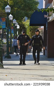 MONTROSE, CA - OCTOBER 5, 2014: Two policemen stroll toward the camera along a quiet tree lined sidewalk in Montrose, California on October 5, 2014.