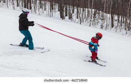 Mont-Tremblant, Quebec, Canada - February 9, 2014: A mother is teaching her young daughter to ski down an easy slope at Mont-Tremblant Ski Resort.