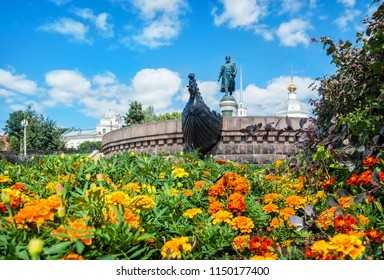 Monument to Afanasiy Nikitin on the blooming embankment of the Volga and the Resurrection Church behind him in Tver on a sunny summer day