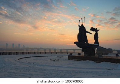 Monument of the Founders of Kyiv, at the bank of River Dnipro (Dnieper). Sunrise at a frosty winter morning. Wide-angle view cityscape. Kyiv, Ukraine.
