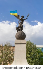 Monument of Independence. Nika the goddess on a ball with a flag of Ukraine in hands on a background of the sky and buildings. City center. May 2018, Kharkiv, Ukraine