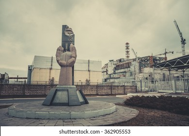 The monument to the liquidators of the Chernobyl accident on the background of the fourth unit of NPP, Pripyat