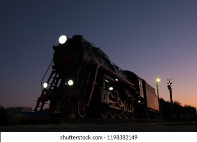 monument to the locomotive against the night sky on a summer day, the old decommissioned mechanism