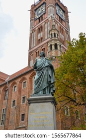 Monument to Nikolai Copernicus 1853 against the background of the clock tower of the old city hall. Torun, Poland