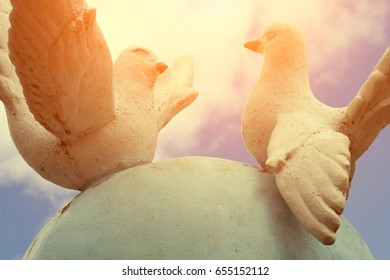Monument of peace - two white pigeons against a blue sky with clouds, Toned photo