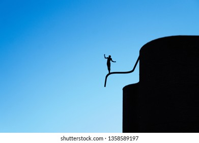 Monument to silhouette of a boy balancing on tube like tightrope walking against background of a blue sky