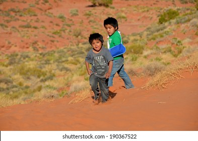 MONUMENT VALLEY ARIZONA APRIL 19: Unidentified navajo children playing in the sand of monument valley on april 19 2104 Arizona USA. The Poverty in Navajo Indian Reservation for family is 46.5%.