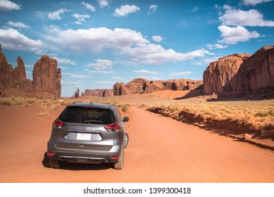 Monument Valley desert, Utah, USA - red sandy floor panorama landscape background. Famous large red sand stone rock domes and buttes with an SUV car silhouette, Utah, Arizona border, U.S. of America