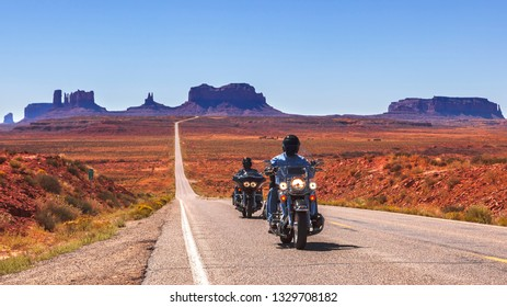 MONUMENT VALLEY, UTAH - SEPTEMBER 22, 2010: Two bikers ride through a desert Monument valley road. Monument Valley Navajo Tribal Park covers 130,000 square miles on the Colorado plateau.