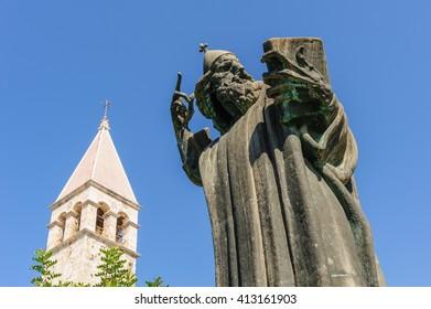 Monumental bronze statue of Bishop Gregory of Nin created in 1929 by Ivan Mestrovic and Saint Rainier Benedict monastery belfry