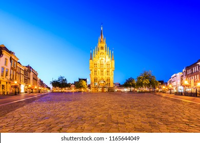 Monumental gothic City hall of the historical city Gouda square, illuminated with lights during dusk under a dark blue sky. One of the oldest Gothic city halls in the Netherlands.