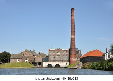 Monumental steam driven factory museum with a long chimney-stalk at a lake