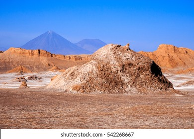 Monuments of stone, mountains and a salt flat in moon valley, Atacama. Licancabur volcano is in the background
