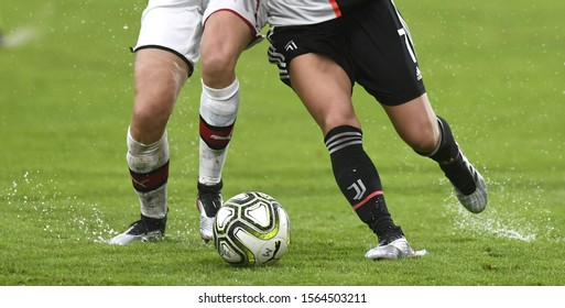 MONZA, ITALY-NOVEMBER 17, 2019: close up legs of female soccer players action, on a wet green soccer field, during the italian soccer match AC Milan vs Juventus FC, in Monza.
