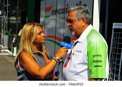 MONZA - SEPTEMBER 11: Vijay mallya of the Force India F1 team is talking to a lady of the press in the paddock on september 11, 2010 in monza, italy