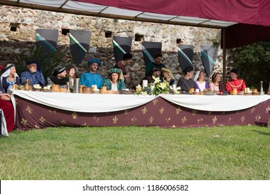 Monzambano, Mantova / Italy - September 16, 2018: medieval sumptuous banquet with rich lords and ladies dressed with elegant clothes of middle ages era, performing in a medieval reenactment in Italy