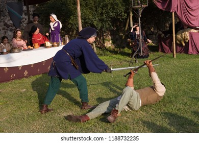 Monzambano, Mantova / Italy - September 16, 2018: end of a duel between two swordmen, one standing and defeating his opponent, the other one lying on the ground during a medieval re-enactment