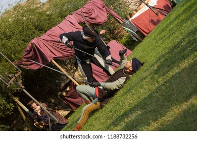 Monzambano, Mantova / Italy - September 16, 2018: medieval reenactment with two noble swordmen measuring swords. One contender defeating his opponent who is lying on the ground