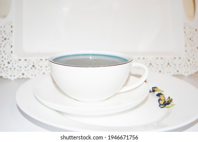 The mood color is blue - blue tea in a white mug, which stands on a white saucer and a white tray. Useful drinks, healing properties. Phytotherapy. Tea party.