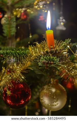 mood full of burning christmas tree candle and christmas bauble close up
