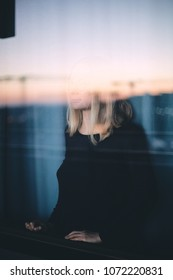 Mood portrait of young blonde woman wearing glasses looking through window enjoying cityscape at sunset - calm and relax in city concept