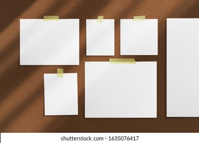 Mood-board composition template with blank photo cards, polaroid frames glued with yellow adhesive tape and on brown desk with geometric  shadow overlay.