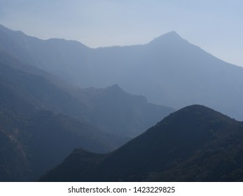 Moody atmospheric landscape of mountain peaks in mist receding into the distance in a remote wilderness