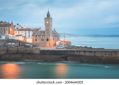Moody, atmospheric night view of the pier and church clock tower at the quaint seaside village of Porthleven, Cornwall, England, UK.
