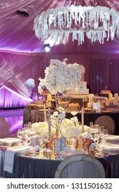 Moody backlit ambience of a wedding reception, luxury elegant table setting