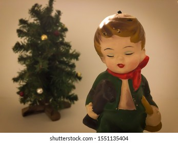 A moody Christmas vignette of a vintage figurine of a little boy holding toys standing in front of miniature Christmas tree with a white background