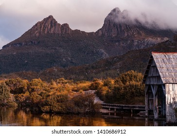 Moody closeup scenery of the famous boatshed with Cradle Mountain as background during sunrise at Dove Lake Circuit, Cradle Mountain - Lake St Clair National Park, Tasmania, Australia.