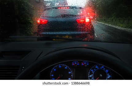 Moody dark image of driving in stormy, wet conditions from the dashboard of a car.