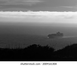 A moody dark image of a tanker entering a harbor, seen from on high with a low fog bank (black and white)