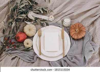 Moody fall table still life. Golden cutlery, olive branches and porcelain plate. Pumpkins, rose hips and pomegranate fruit. Blank menu card mockup. Autumn, Thanksgiving and Rosh Hashanah concept.