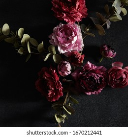 Moody floral concept - flower on dark textured background. Top view, square composition