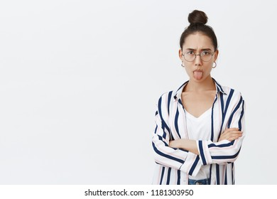 Moody girl showing character, expressing dislike, unwilling go home from party. Good-looking feminine woman in stylish shirt, holding hands crossed on chest and sticking out tongue childishly