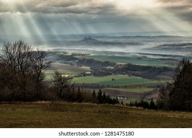 Moody highland landscape with castle ruins in stormy weather with sun rays on horizon, bare trees and meadow in the foreground in cold autumn. Czech Paradise, view from Kozakov hill on hills, meadows