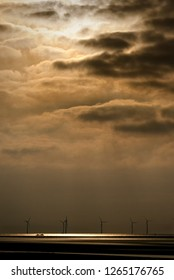 A moody image with interesting light showing the juxtaposition of an old shipwreck against the modernity of the windfarm. The wreckage is the remains of the cargo ship Ionic Star.