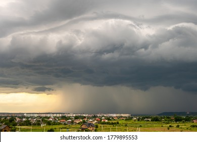 Moody landscape with dark stormy clouds with falling heavy downpour shower rain over distant town buildings in summer.