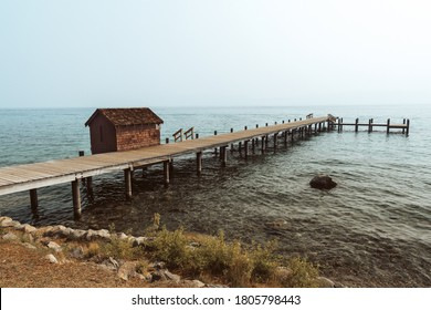 Moody landscape scene of a pier and boathouse on Lake Tahoe during sunset at Sugar Pine State Park near Tahoma, California